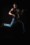 音乐和创造性 T恤杉和牛仔裤的英俊的年轻人,跳跃与一把电吉他,在黑色被隔绝的背景 免版税图库摄影