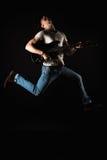 音乐和创造性 T恤杉和牛仔裤的英俊的年轻人,跳跃与一把电吉他,在黑色被隔绝的背景 免版税库存照片