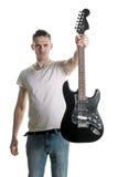 音乐和创造性 T恤杉的一个英俊的年轻人在他的手上提供一把电吉他 玩它 水平的框架 库存图片