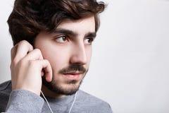 音乐和技术概念 听到audiobook或收音机的一个时髦的行家在手机有看在旁边touchin的耳机的 免版税库存照片
