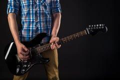 音乐和艺术 吉他弹奏者在他的手上拿着一把电吉他,在黑色被隔绝的背景 吉他使用 水平的fra 库存图片