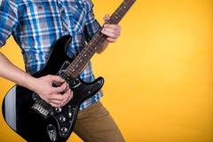音乐和艺术 吉他弹奏者弹在黄色被隔绝的背景的电吉他 吉他使用 水平的框架 免版税库存图片
