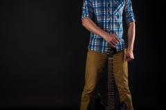 音乐和艺术 吉他弹奏者拿着在他的右手的一把电吉他,在黑色被隔绝的背景 吉他使用 horizonta 免版税库存照片