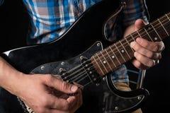 音乐和艺术 电吉他在一个吉他弹奏者的手上,黑色被隔绝的背景的 吉他使用 水平的框架 图库摄影