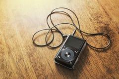 音乐在一张木书桌上的MP3播放器 免版税库存照片