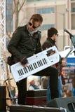 音乐家举行和戏剧合成器喜欢在音乐会的一把吉他 库存照片