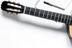 音乐家书桌歌曲作者工作的设置了与吉他和纸白色背景顶视图大模型 免版税库存照片
