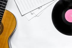 音乐家书桌歌曲作者工作的设置了与吉他和纸,唱片白色背景顶视图大模型 库存照片