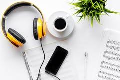 音乐家书桌歌曲作者的与耳机和智能手机一起使用在白色背景顶视图大模型 库存照片