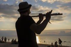 音乐家人戏剧在日落的长笛在一个满月党期间的海滩在海岛酸值Phangan,泰国 免版税库存图片