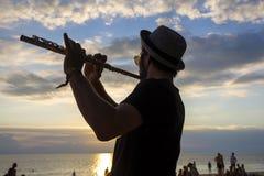 音乐家人戏剧在日落的长笛在一个满月党期间的海滩在海岛酸值Phangan,泰国 免版税库存照片