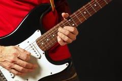 音乐家在黑背景的电吉他上把弦的手指放 库存图片
