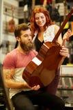 音乐家夫妇有吉他的在音乐商店 图库摄影
