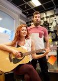 音乐家夫妇有吉他的在音乐商店 免版税库存照片