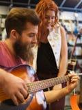音乐家夫妇有吉他的在音乐商店 免版税库存图片