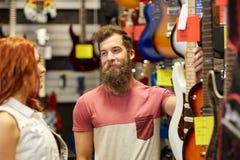音乐家夫妇有吉他的在音乐商店 库存图片