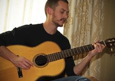 音乐家弹一把古典声学吉他 免版税图库摄影