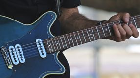 音乐家弹一把蓝色电吉他 免版税库存照片