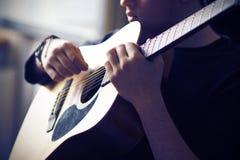 音乐家弹他的声学吉他,举行fretboard在基地 免版税图库摄影