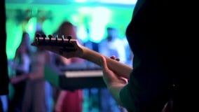 音乐家弹吉他在音乐会 吉他弹奏者握他的在吉他身分的脖子的手在阶段的 影视素材