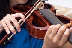 弹小提琴,乐器用执行者手 免版税库存图片