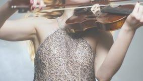 音乐家执行者到使用在无意识而不停地拨弄的华美的礼服里在闪光灯的乐队 影视素材