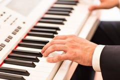 音乐家特写镜头的手 使用在电钢琴的钢琴演奏家 免版税库存图片