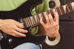 音乐家的手投入了吉他弦紧密  免版税库存照片