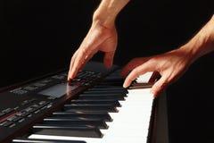 音乐家的手播放合成器的钥匙在黑背景的 免版税库存图片