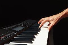 音乐家的手播放电子合成器的钥匙在黑背景的 免版税库存图片