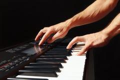 音乐家的手播放synth的钥匙在黑背景的 库存图片