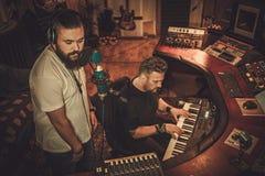 音乐家记录声音和键盘在精品店录音室 免版税库存图片