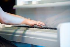 音乐执行者的手的特写镜头弹钢琴的 库存照片