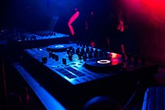 音乐搅拌器控制器在聚光灯下光的音乐控制DJ在夜总会的摊 免版税库存图片