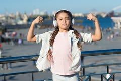 音乐有医治用的力量 可爱的孩子享受使用在都市背景的耳机的音乐 享用她的女孩 免版税库存照片