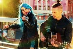 音乐有女孩小提琴手日落都市风景的街道执行者 免版税库存照片