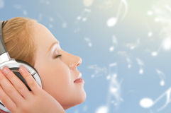 音乐概念。 妇女享受在天空背景wi的音乐 免版税库存图片
