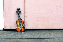 音乐激情和爱好概念,在木墙壁的小提琴缩样有减速火箭的颜色口气的 免版税图库摄影