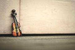 音乐激情和爱好概念,在木墙壁的小提琴缩样有减速火箭的颜色口气的 免版税库存照片