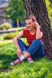 音乐激情愉快的妇女听到音乐通过耳机和智能手机在公园 库存照片