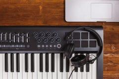 音乐生产规定密地琴键视网膜膝上型计算机黑色在木书桌桌上的dj耳机 顶视图 库存图片