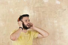 音乐生活方式 快乐的dj听的歌曲通过耳机 欧洲人有乐趣时间 美国英俊的有胡子的人 免版税库存照片