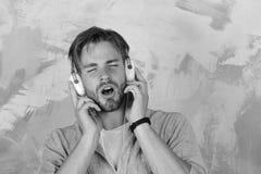 音乐生活方式 有智能手机的蓝眼睛的时髦的行家 有耳机的美国英俊的有胡子的人 欧洲 库存照片