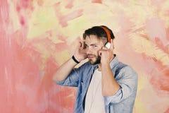 音乐生活方式 有智能手机的蓝眼睛的时髦的行家 有耳机的美国英俊的有胡子的人 免版税库存图片