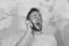 音乐生活方式 欧洲人有乐趣时间 有耳机的美国英俊的有胡子的人 库存图片