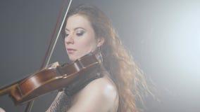 音乐界,有长的头发的有天才的小提琴手执行古典音乐在交响乐音乐会 股票视频