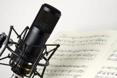 有音乐纸张的演播室话筒 免版税库存图片