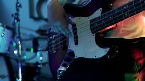 音乐视频废物、重金属或者摇滚小组 弹低音吉他的男性手特写镜头视图活在蓝色的展示期间 股票录像