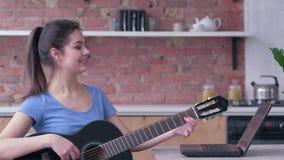 音乐训练,快乐的艺术家女性实践的戏剧吉他使用有网上录影讲解的手提电脑并且采取 股票录像
