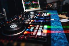 音乐设备和演奏音乐的DJ搅拌器在夜总会在党和醒目的作用 免版税库存照片